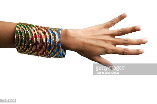 Woman's hand with many bangles on her wrist