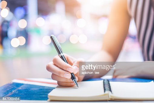 Woman's hand writing on a notebook with a pen on a wooden desk. : Stock Photo