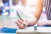 Woman's hand writing on a notebook with a pen on a wooden desk.Background blur backlight