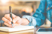 Woman's hand writing on a notepad with a pen on a wooden desk.