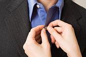 Woman's hands buttoning man's shirt