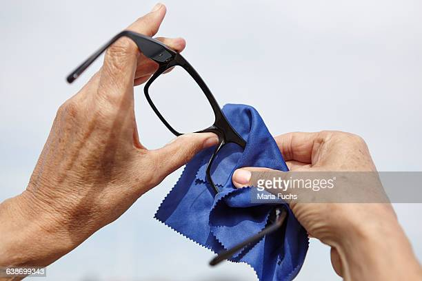Womans hands cleaning eye glasses with cloth