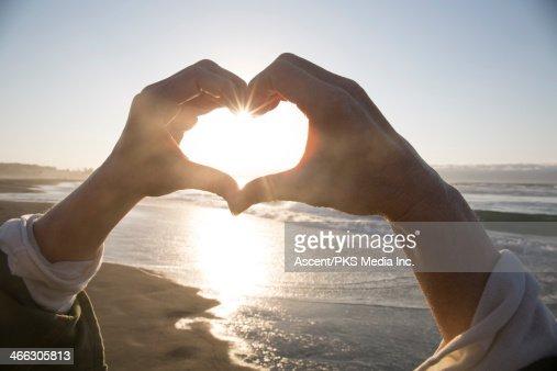 Woman's hands create heart shape, above ocean surf