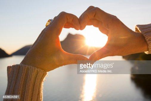 Woman's hands create heart shape at lake, sunrise : Stock Photo