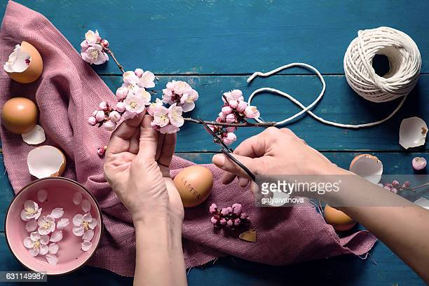 Womans hands cutting making easter decoration
