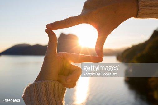 Woman's hands frame sunrise over mountain lake