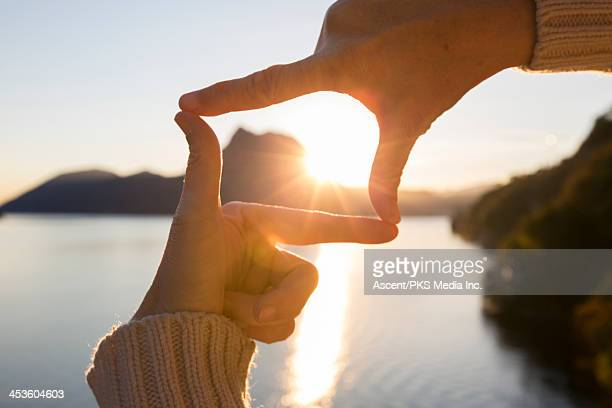 Woman's hands frame sunrise over mountain lake