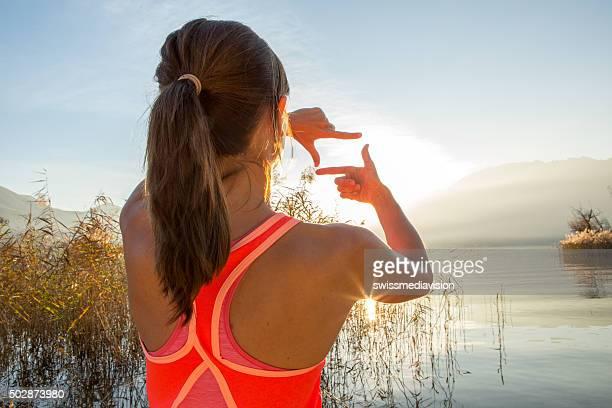 女性の手のフレームの夕暮れの湖
