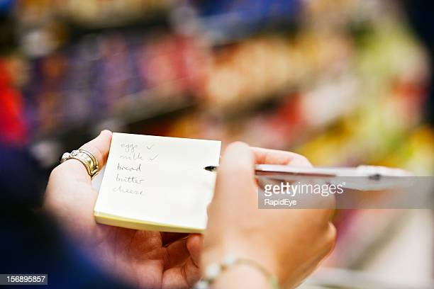 Woman's hands hold pen as she checks her shopping list