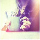 A woman's hands holding a blue mug