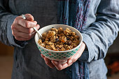 High resolution, digital capture of a woman's hands holding a bowl filled with homemade granola. Granola consists of oats, cashews, almonds, dried apricots, dried papaya, dried cranberries, honey, coc