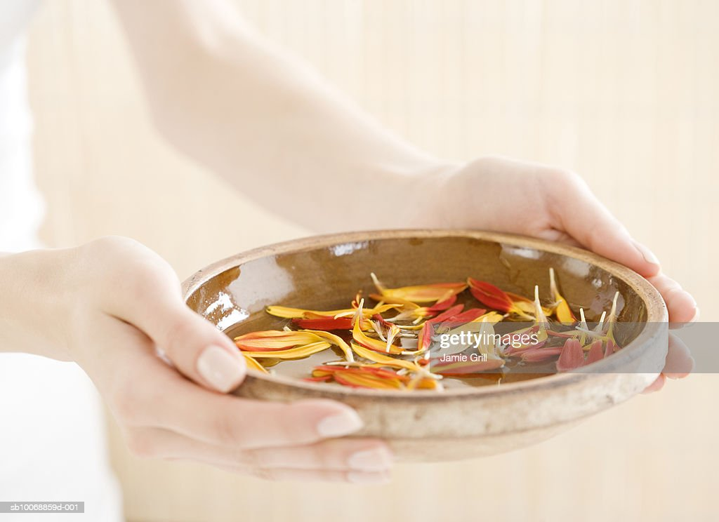 Woman's hands holding bowl of flower petals, close-up : Stock Photo