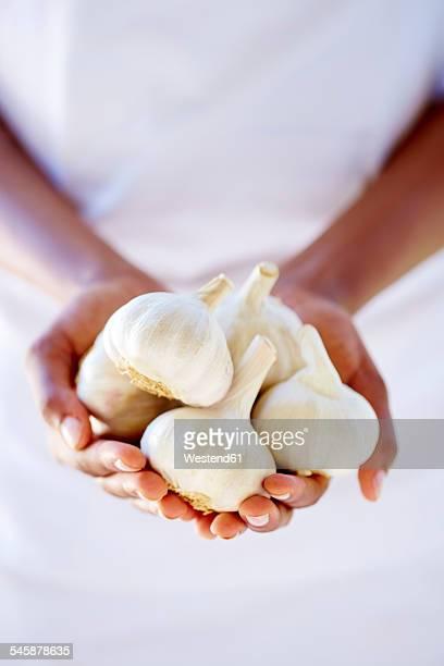 Womans hands holding garlic bulbs
