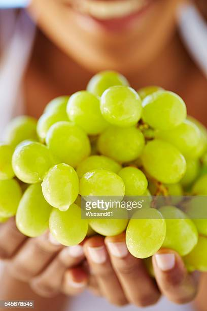Womans hands holding green grapes