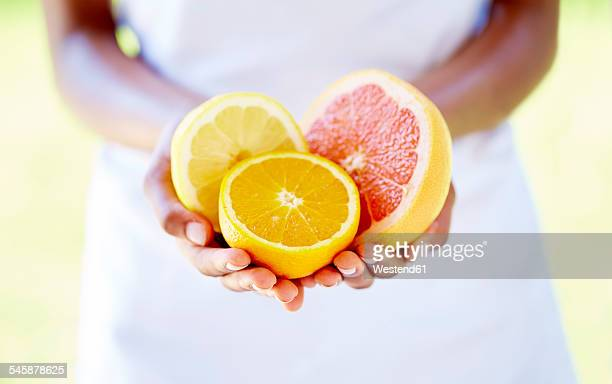 Womans hands holding halves of orange and grapefruit