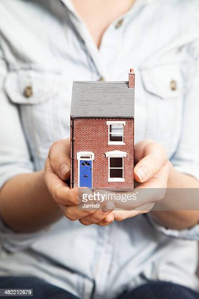 Woman's hands holding model house