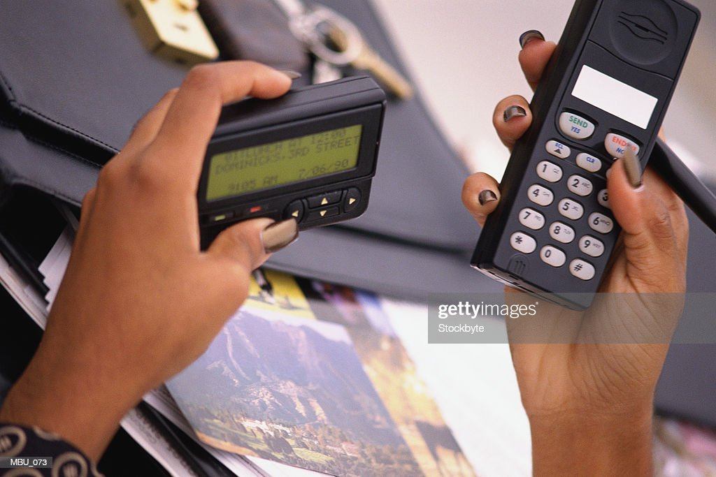 Woman's hands holding pager and cellular phone