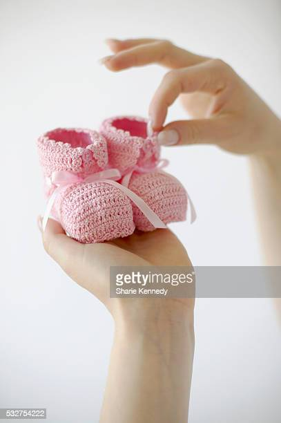 Woman's Hands Holding Pink Baby Shoes