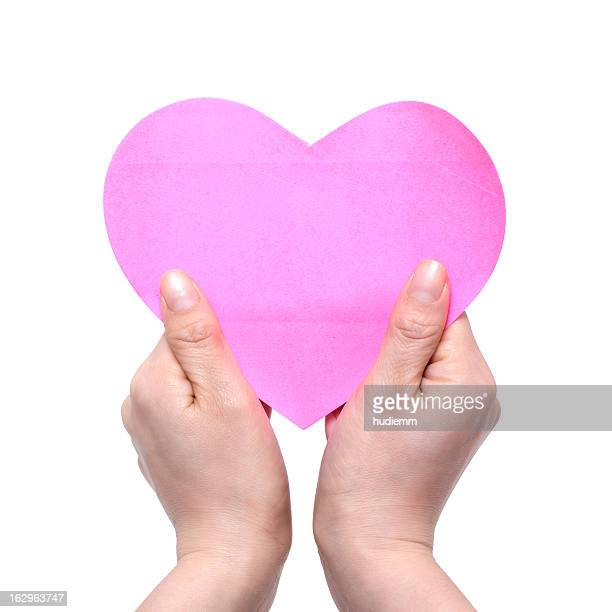 Woman's Hands Holding pink Heart isolated on white background