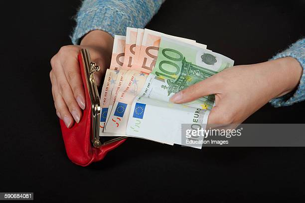 Woman's hands holding red purse and high denomination Euro banknotes