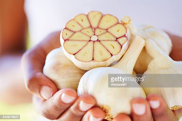 Womans hands holding whole and sliced garlic bulbs