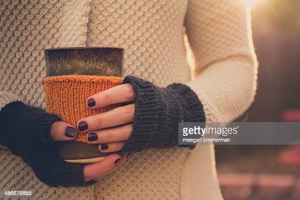 Woman's hands in knits holding pottery