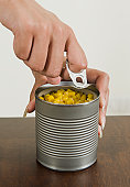 Woman's hands opening a can of sweet corn