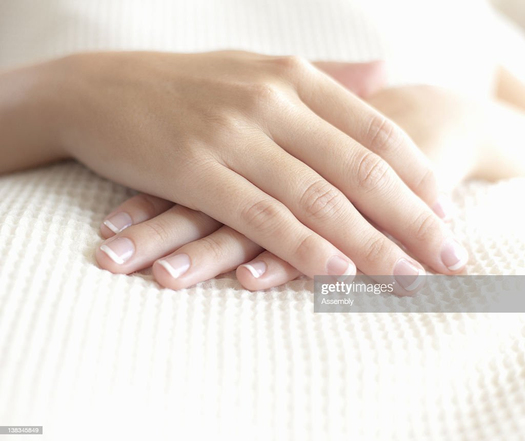 Woman's hands resting on stomach : Stock Photo