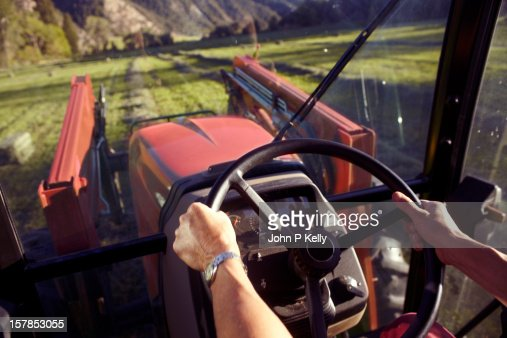 Woman's hands steering tractor : Stock Photo