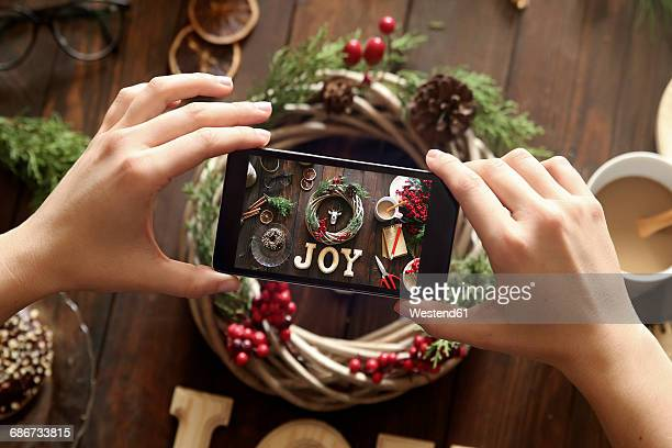Womans hands taking picture of self-made Advent wreath with smartphone