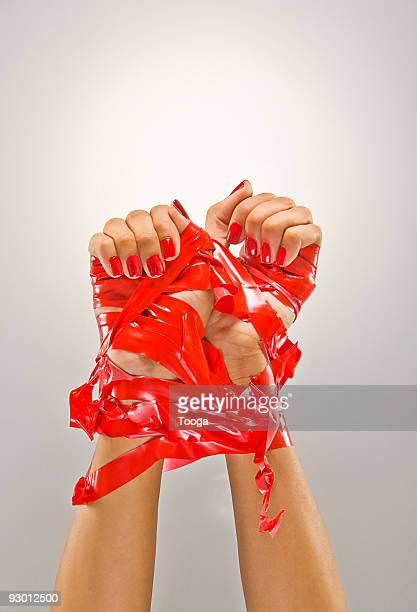 Woman's hands tied up with red tape