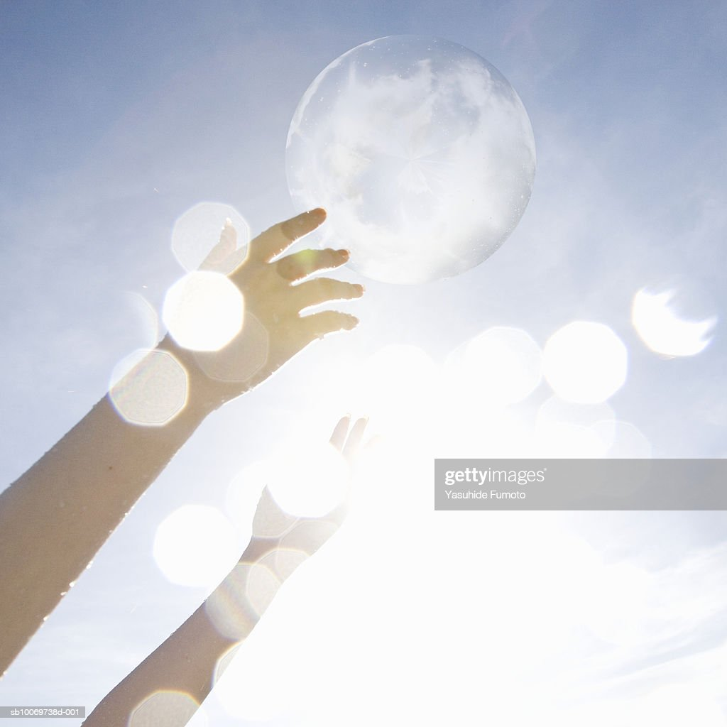 Woman's hands touching bubbles in sky : Stock Photo