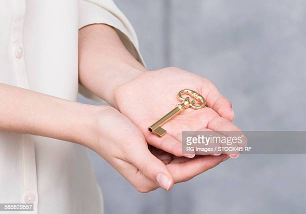 Womans hands with golden key