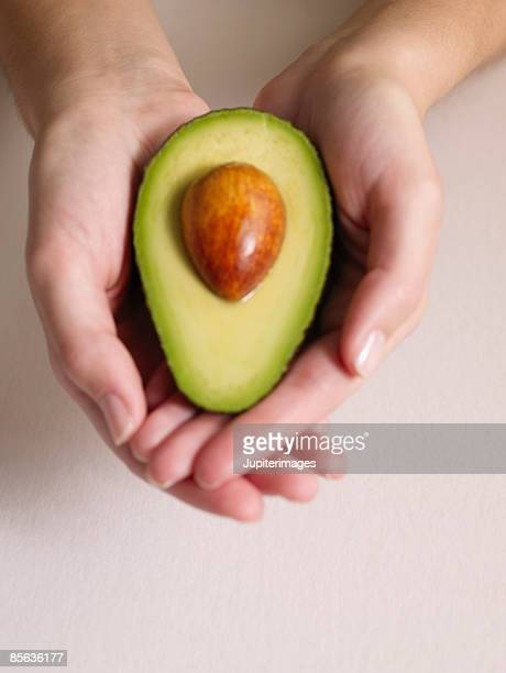 Woman's hands with halved avocado