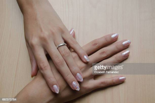 Woman's hands with pastel metalic manicure.