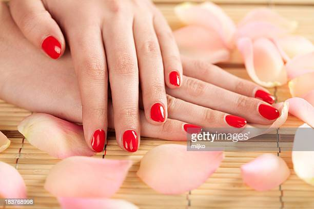 Woman's hands with red fingernails on bamboo table