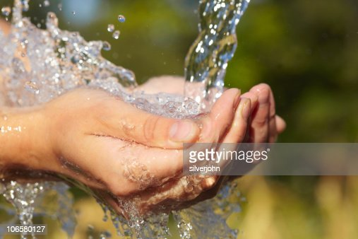 Woman's hands with water splash : Stock Photo