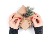 Woman's hands wrapping Christmas gift box with fir branches and pine cone.
