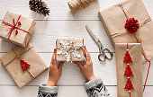 Creative hobby. Woman's hands show christmas holiday handmade present in craft paper with twine ribbon. Making bow at xmas gift box, decorated with snowflake. Scissors on white wooden table, top view.