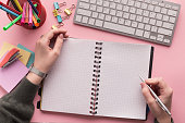 Woman's hands writing in spiral notepad as mockup for your design on pink background with keyboard and stationery, top view. Girlish workplace, lifestyle concept with copy space