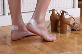 Woman's heel with blister plaster / band-aid on cloe up. Prevent New Shoes From Giving Blisters.