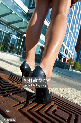 Woman's high heel shoe trapped in sidewalk grate