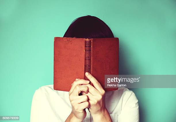 Woman's holding a book in front of her face