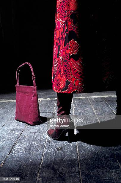 Woman's Leg with Bag and Boots on Wooden Floor