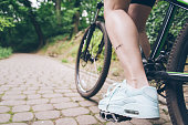 womans leg with dirty of oil from chain on bicycle stop in sity park