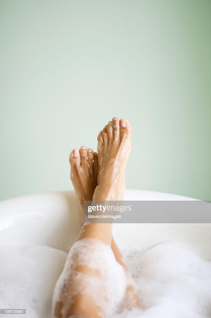 Femmes jambes et des pieds avec des bulles dans la baignoire : Photo