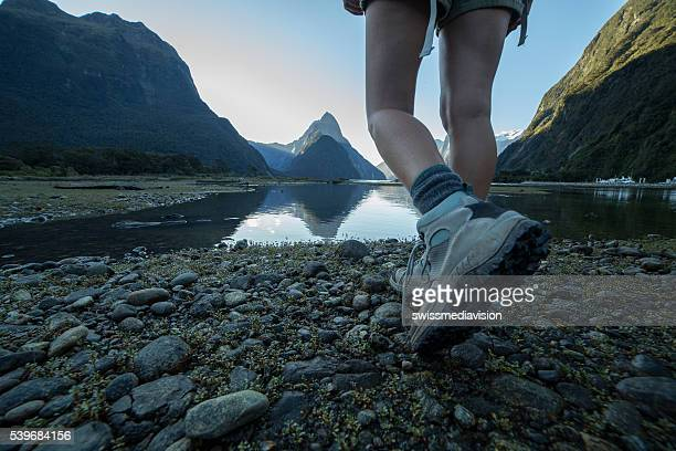 Woman's legs and hiking boots standing on rocky trail