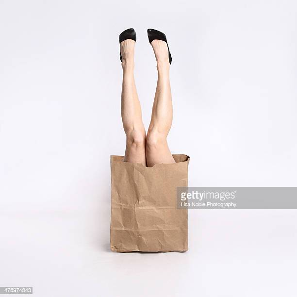 Woman's legs coming out of a brown paper bag