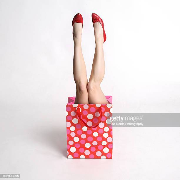 Woman's legs coming out of a festive gift  bag