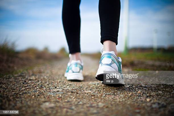 Woman's legs in black tights and white running shoes on dirt
